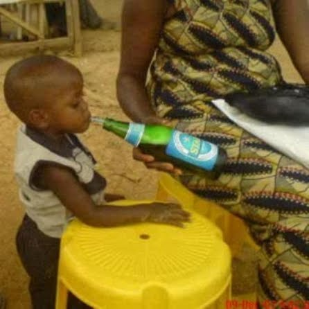 Mother teaching child how to drink beer